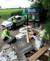 Uniformed officers dealing with flytipping on country road