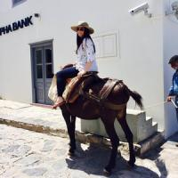 Kate Ford poses on a donkey in Greece.